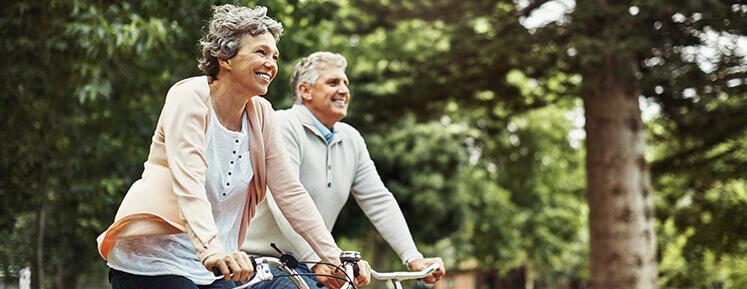 happy senior couple biking together